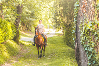 Woman riding horse on tree lined dirt track, looking at camera
