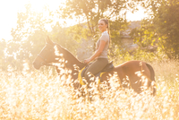 Side view of woman riding horse looking at camera smiling