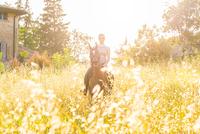 Woman riding horse looking at camera smiling 11015290884| 写真素材・ストックフォト・画像・イラスト素材|アマナイメージズ