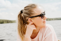 Woman wearing sunglasses looking over her shoulder to lake, Orivesi, Finland