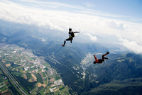 Freestyle skydiving team training together. One man  performing air-ballet, another jumper is filming with video camera on helme 11015290953| 写真素材・ストックフォト・画像・イラスト素材|アマナイメージズ