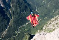 Wingsuit BASE jumper is flying down, Italian Alps, Alleghe, Belluno, Italy