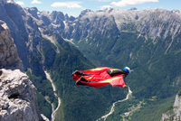 Wingsuit BASE jumper flying along cliff side and down the valley, Italian Alps, Alleghe, Belluno, Italy