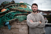 Portrait of young fisherman leaning against crate of fishing nets in harbour, Fraserburgh, Scotland 11015290991| 写真素材・ストックフォト・画像・イラスト素材|アマナイメージズ