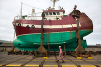 Male ship painter walking in front of fishing boat on drydock
