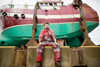 Male ship painter sitting in front of fishing boat on drydock