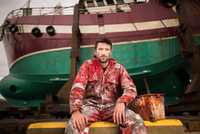 Portrait of male ship painter sitting in front of fishing boat on drydock