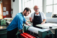Senior craftsman/technician supervising young man on letterpress machine in book arts workshop 11015294031| 写真素材・ストックフォト・画像・イラスト素材|アマナイメージズ