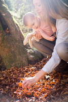 Mother and daughter crouching investigating leaves on forest floor