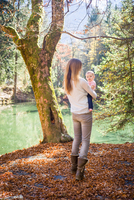 Rear view of mother and baby girl in forest by water