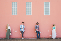 Friends standing against pink wall background