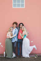Couples hugging against pink wall background
