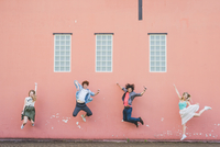 Friends jumping against pink wall background