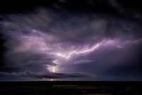 Lightning sparks from a spinning supercell thunderstorm at night near Leoti, Kansas