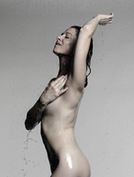 Naked mature woman showering with hand on chest and arm raised