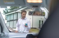 Man charging electric car, seen through car interior 11015294565| 写真素材・ストックフォト・画像・イラスト素材|アマナイメージズ
