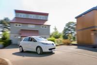 Electric car driving through neighbourhood 11015294578| 写真素材・ストックフォト・画像・イラスト素材|アマナイメージズ