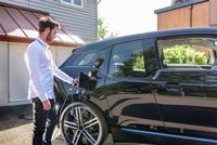 Man charging electric car 11015294581| 写真素材・ストックフォト・画像・イラスト素材|アマナイメージズ
