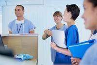 Medical staff chatting at nurses station in hospital 11015294774| 写真素材・ストックフォト・画像・イラスト素材|アマナイメージズ