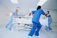 Doctor and medical running with patient bed in hospital emergency