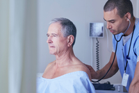 Male nurse listening to senior male patient back with stethoscope