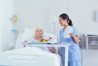 Nurse serving lunch to senior female patient in hospital bed