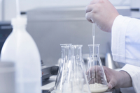 Scientist pipetting sample into beaker in laboratory