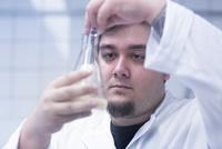 Scientist pipetting sample into beaker in laboratory