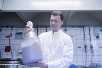 Scientist carrying large bottle of chemical in laboratory