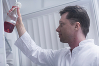 Scientist removing bottle of liquid from cabinet