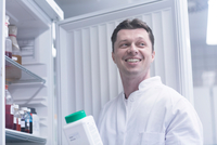 Scientist holding bottle of chemical removed from cabinet