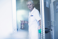 Scientist carrying rack with petri dishes in laboratory