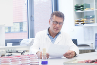 Scientist reading test results in laboratory