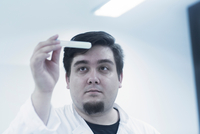 Scientist examining sample in test tube