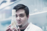 Scientist examining sample in beaker