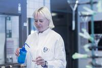 Scientist pipetting liquid into flask in laboratory