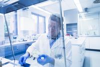 Scientist examining sample inside petri dish in laboratory