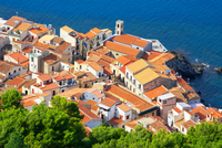 High angle view of Cefalu terracotta rooftops and coast from La Rocca, Sicily, Italy