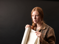 Portrait of young female designer holding rolled fabric