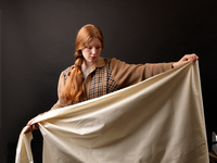 Young female designer inspecting rolled fabric