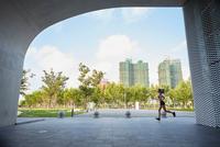 Woman jogging in urban area, South Bund, Shanghai, China
