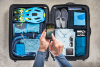 Overhead view of man's hands using smartphone touchscreen above packed suitcase with blue bike helmet, backpack, retro camera an 11015295429| 写真素材・ストックフォト・画像・イラスト素材|アマナイメージズ
