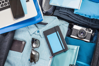 Overhead detail of packed suitcase with blue shirt,  retro camera, laptop, smartphone and notebook