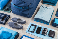 Overhead view of travel packing with blue shirt,  retro camera, training shoes, smartphone and notebook