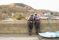 Rear view of two kayakers looking out from bridge on River Dee, Llangollen, North Wales