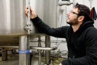 Worker in brewery, checking pressure gauge on brew tank