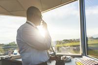 Pilot in control tower of small airport, using telecommunications system