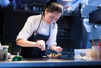 Chef in commercial kitchen seasoning food 11015296028| 写真素材・ストックフォト・画像・イラスト素材|アマナイメージズ