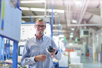 Portrait of engineer holding 3D printed exhaust valve actuator in factory 11015296050| 写真素材・ストックフォト・画像・イラスト素材|アマナイメージズ