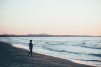 Woman strolling on beach at dusk, Sorso, Sassari, Italy